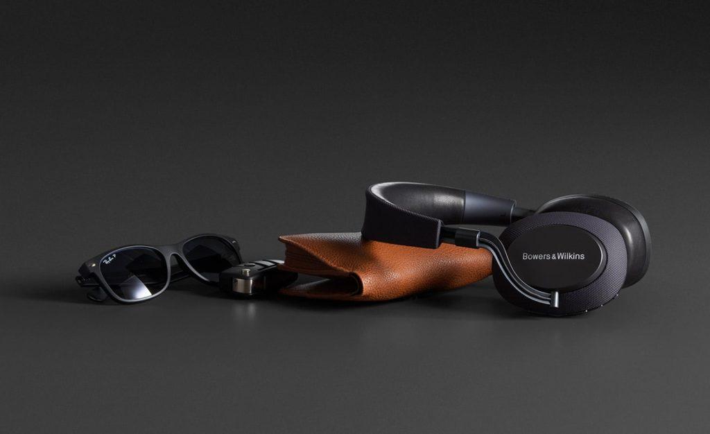 Bowers & Wilkins PX modèle noir, illustration avec des lunettes et une pochette en cuir